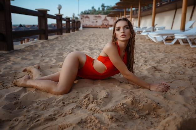 Модное фото на открытом воздухе красивой чувственной женщины с длинными темными волосами в элегантном оранжевом купальнике, расслабляющейся у бассейна