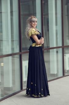 夏の町でポーズ豪華なスパンコールのドレスで長い髪の美しい官能的な女性のファッション屋外写真