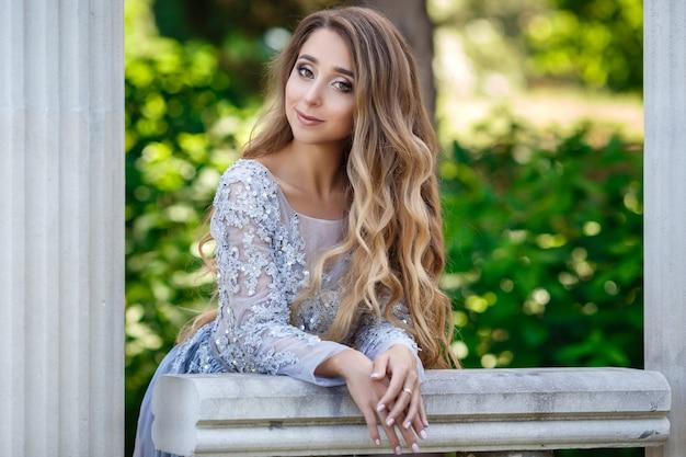 夏の公園でポーズをとって、豪華なスパンコールのドレスとシルバーのアクセサリーでブロンドの髪を持つエレガントな美しい女性のファッション屋外写真