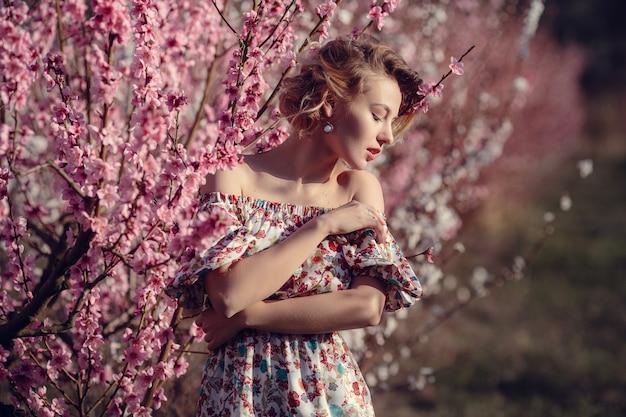 花の桃の木と庭でポーズをとってエレガントなドレスを着たゴージャスな若い女性のファッション屋外写真。花の咲く庭園で金髪