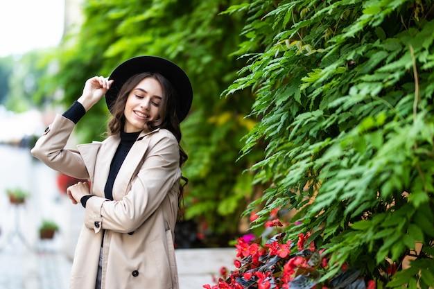 Foto di moda all'aperto di giovane donna graziosa in abito elegante e cappello nero che cammina per strada