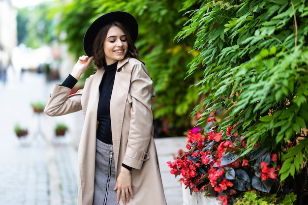 Fashion outdoor photo of young pretty woman in elegant outfit and black hat walking on the street