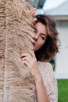 Fashion outdoor portrait of brunette short hair woman with broom