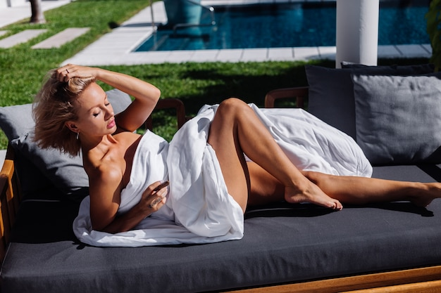 Fashion outdoor portrait of naked woman sits on sofa covering herself with blanket holding cigar