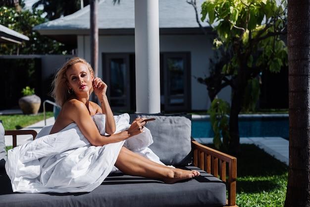 Moda ritratto all'aperto di donna nuda si siede sul divano coprendosi di coperta tenendo il sigaro