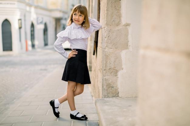 白いブラウスと黒いスカートの魅力的な少女のファッション屋外のポートレート、古代ヨーロッパの都市の美しい古い建物の壁に寄りかかってポーズします。水平ショット、コピースペース