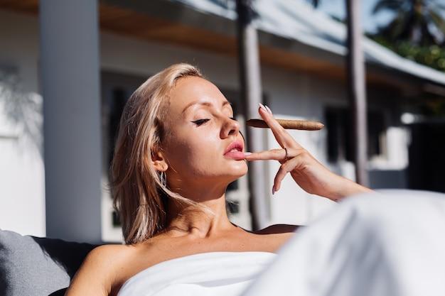 Модный открытый портрет обнаженной женщины сидит на диване, накрываясь одеялом, держа сигару
