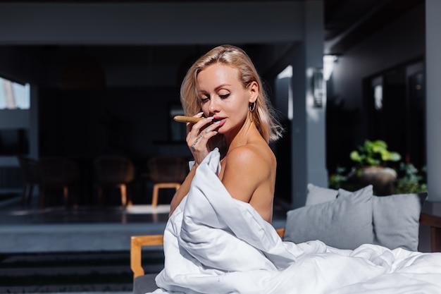 벌거 벗은 여자의 패션 야외 초상화는 시가를 들고 담요로 자신을 덮고 소파에 앉아