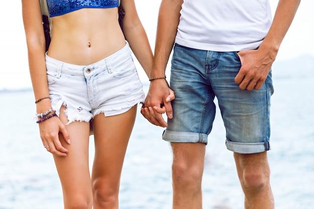彼女のガールフレンドの手を握って若い男のファッション屋外のポートレート、愛の流行に敏感な若いカップルは、海辺でポーズをとって、一緒に夏の旅行をお楽しみください。