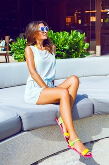Fashion outdoor portrait of pretty tan sportive woman relaxed and enjoy sunny hot day at her vacation on luxury resort, wearing casual beach dress and sunglasses. bright sunny colors.