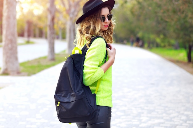 Fashion outdoor portrait of young pretty stylish hipster woman wearing trendy neon sweater sunglasses and vintage hat, traveling with backpack. street style fall autumn look.