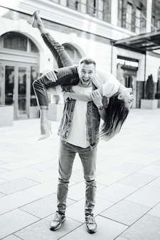 Fashion outdoor romantic portrait of beautiful young couple in love kissing and hugs on the street. wearing stylish fall outfit ,black leather bag and coat.