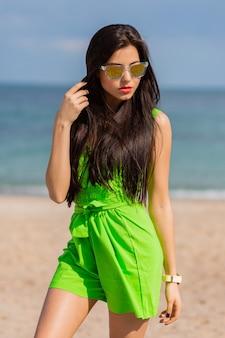 Adatti il ritratto di estate all'aperto di bella donna castana abbastanza giovane in occhiali da sole freddi che posano sulla spiaggia tropicale soleggiata.