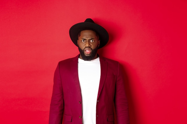 Fashion and party concept. confused black man in classy outfit frowning and staring at camera displeased, cant understand, standing over red background