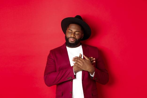 Concetto di moda e festa. giovane uomo di colore barbuto con cappello e giacca di classe, tenendosi per mano sul cuore e sorridendo nostalgico, ricorda qualcosa, sognando ad occhi aperti su sfondo rosso