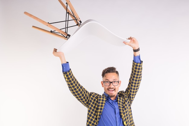 Fashion and people concept - handsome man in glasses twisting with chair on white wall.