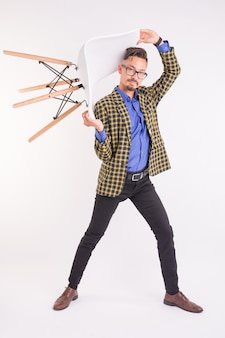 Fashion and people concept - handsome man in glasses twisting with chair.