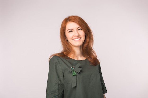 Fashion and people concept. portrait of happy ginger woman smiling looking directly over white