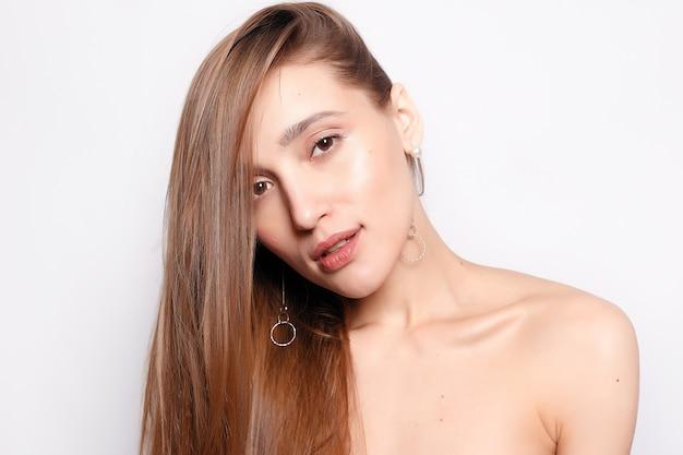 ファッション、人、若者、美容のコンセプト-自然なメイク、きれいな肌、灰色の背景に白い歯を持つ美しい笑顔の女性。自然な肌を持つ女性の顔の美しさの肖像画
