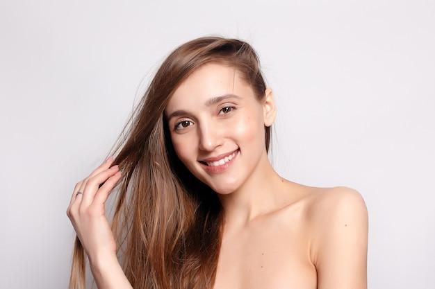 Концепция моды, людей, молодости и красоты - красивая улыбающаяся женщина с естественным макияжем, чистой кожей и белыми зубами на сером фоне. красота портрет женского лица с натуральной кожей