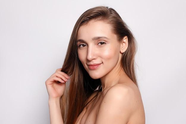 ファッション、人々、若さと美しさの概念-自然なメイク、きれいな肌、灰色の背景に白い歯を持つ美しい笑顔の女性。自然な肌を持つ女性の顔の美しさの肖像画