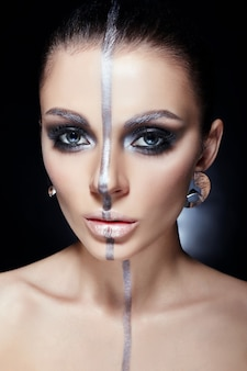 Fashion perfect makeup, silver color band on girl face, silver eyebrows and black brunette hair.