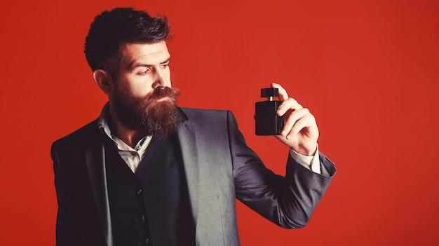 ファッション香水瓶。男の香水、香り。香水のボトルを保持しているひげを生やした男。男性的な香水。香水またはケルンのボトル。男性の香りと香水、化粧品。