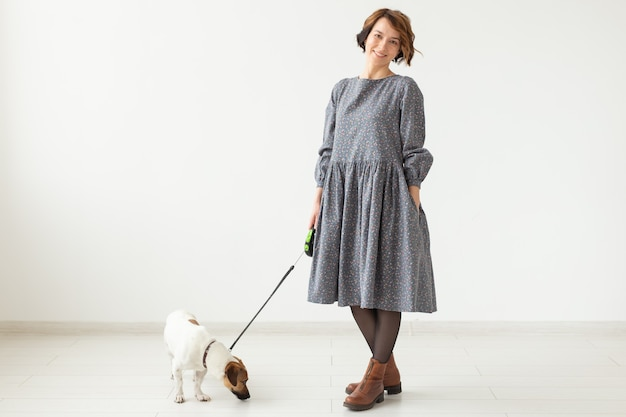 Fashion and pet's owner concept - young woman posing in clothes with jack russell