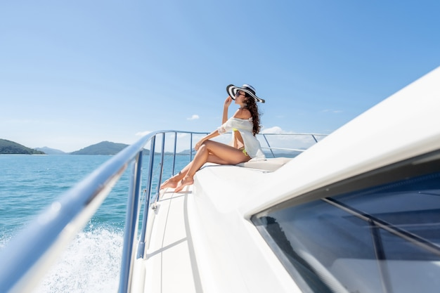 Fashion photo of adorable young woman sitting on edge of luxury yacht and looking for the sea during sailing trip