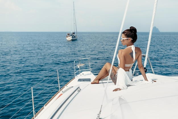Fashion photo of adorable young woman in white swimsuit and cape sitting on yacht