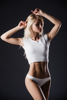 Fashion photo of beautiful blonde fit woman with magnificent hair posing on grey