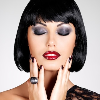 Fashion photo of a beautiful brunette woman with shot hairstyle. closeup girl's face with red lips and nails