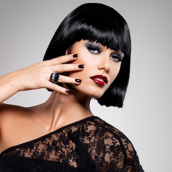 Fashion photo of a beautiful brunette woman with shot hairstyle. closeup girl's face with red nails