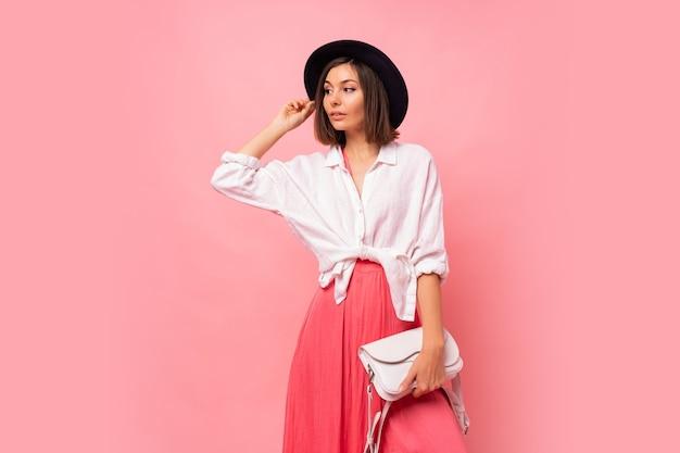 Foto di moda della donna castana graziosa nella posa dell'attrezzatura di primavera borsa bianca della tenuta.