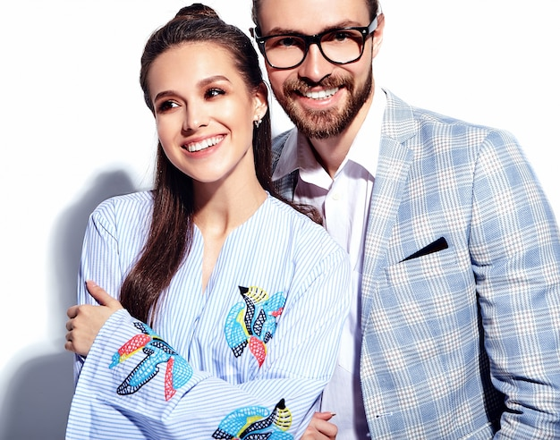Fashion photo of handsome elegant man in glasses in suit with beautiful sexy woman in colorful dress on white Free Photo