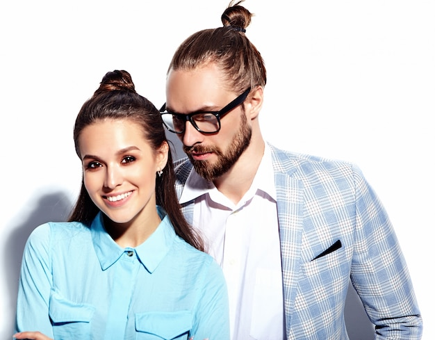 Fashion photo of handsome elegant man in glasses in suit with beautiful sexy woman in colorful dress on white