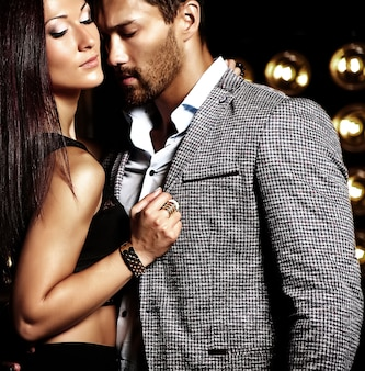 Fashion photo of handsome  elegant man in suit with beautiful sexy woman posing on black studio lights background