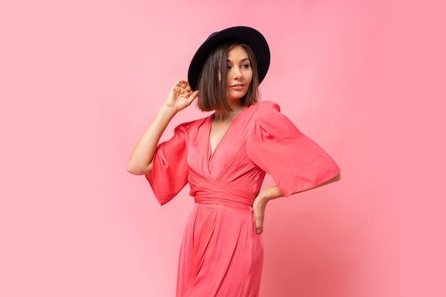 Foto di moda di bella donna bruna in abito rosa in posa