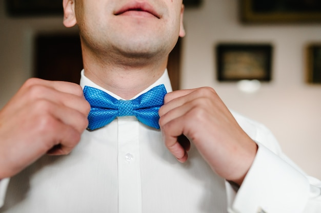 Fashion photo of a man, man's hands touches bow-tie on a suit correcting his bowtie. morning preparation groom at home.