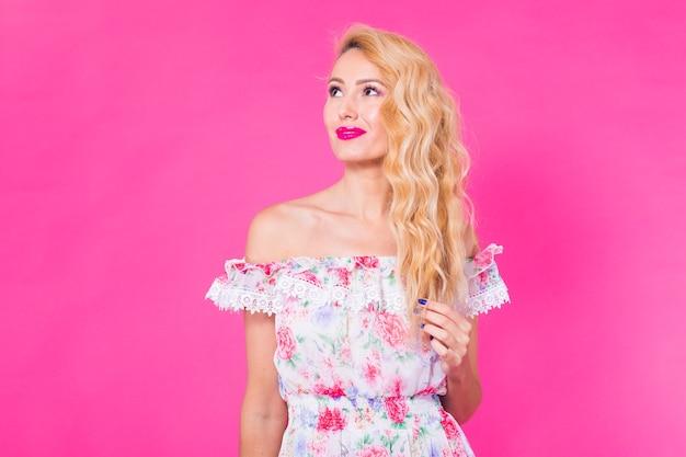 핑크 벽 위에 포즈 예쁜 드레스에 아름 다운 우아한 젊은 여자의 패션 사진