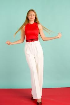 かなり赤いタンクトップ、白いズボン、青い背景の上にポーズをとってハイヒールの美しいエレガントな若い女性のファッション写真。