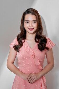 Фасонируйте фото красивой молодой женщины в красивом платье с горошек, позирующим на сером фоне. модное фото