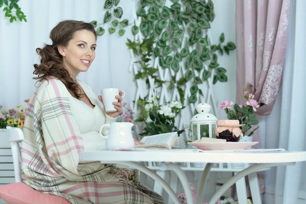 飲み物とスタジオのインテリアでポーズをとって長い黒髪の美しい妊婦のファッション写真