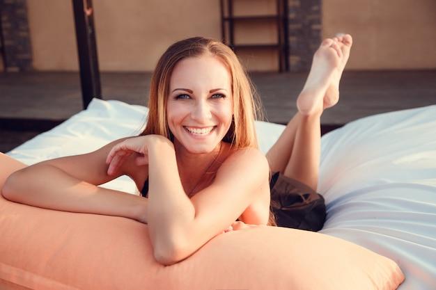 Фасонируйте фото красивой загорелой женщины с рыжими волосами в элегантном черном бикини, расслабляющемся у бассейна