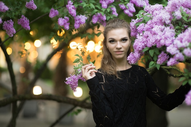 봄 꽃으로 둘러싸인 아름다운 젊은 여성의 패션 사진 프리미엄 사진
