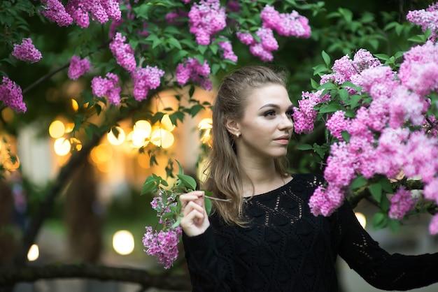 봄 꽃으로 둘러싸인 아름다운 젊은 여성의 패션 사진