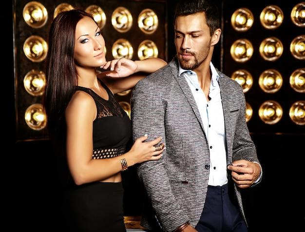 Фасонируйте фото красивого элегантного человека в костюме при красивая сексуальная женщина представляя на черной предпосылке светов студии