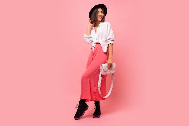 Фасонируйте фото симпатичного представлять обмундирования женщины брюнет весной держа белую сумку. полная длина.