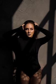 彼女の影の窓の近くの官能的な女性のファッション写真