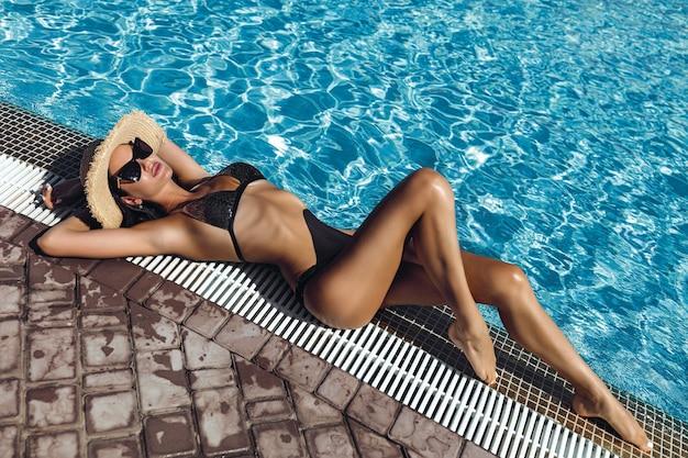 Модная фотография сексуальной красивой девушки в черном бикини, расслабляющейся у бассейна